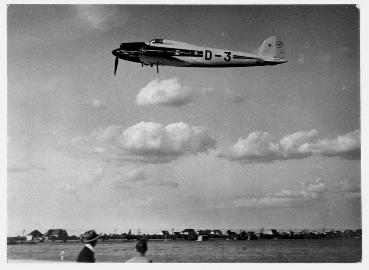 Ett fly i lufta, Heinkel HE 70, D-3 fra Lufthansa. Bygninger under.