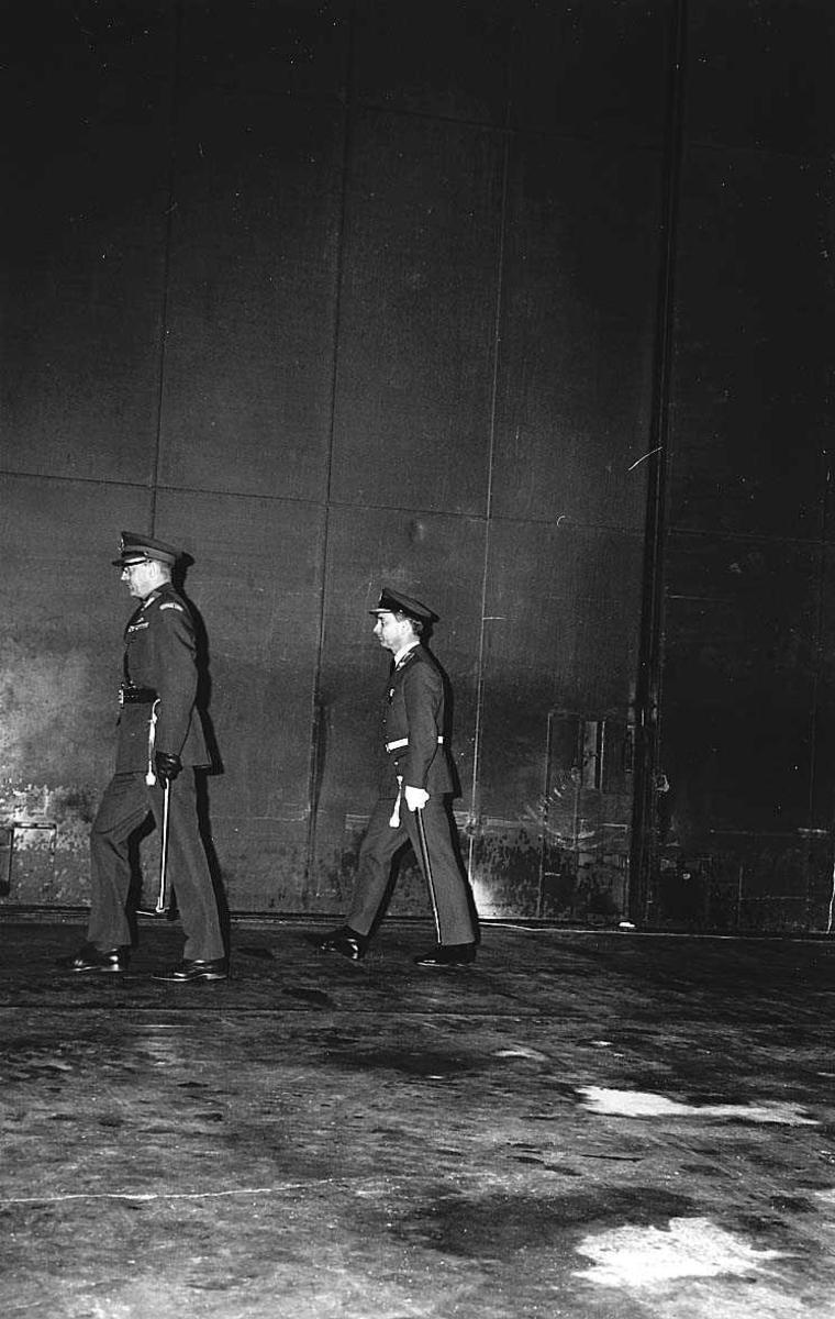 2 offiserer på oppstilling i en hangar.