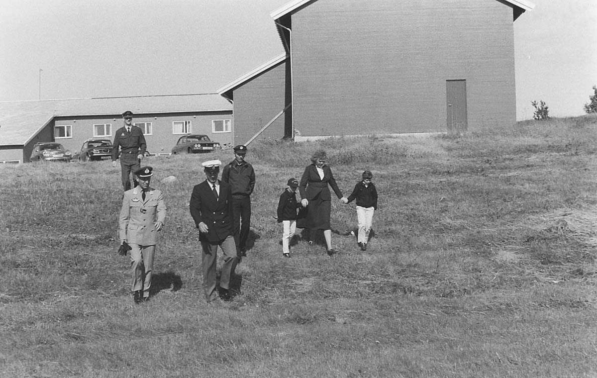 7 personer spaserer på marken. Bygninger og biler i bakgrunnen.
