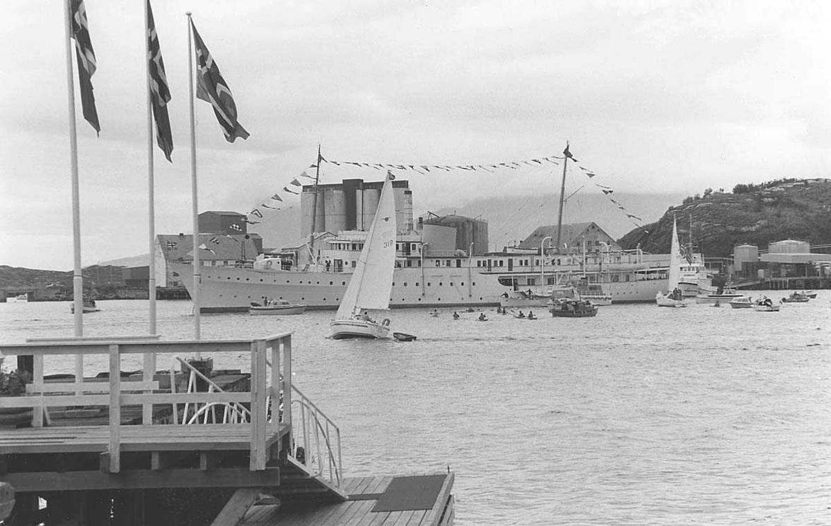 En båt er forankret på en havn. Bygninger, siloer og tankanlegg i bakgrunnen.