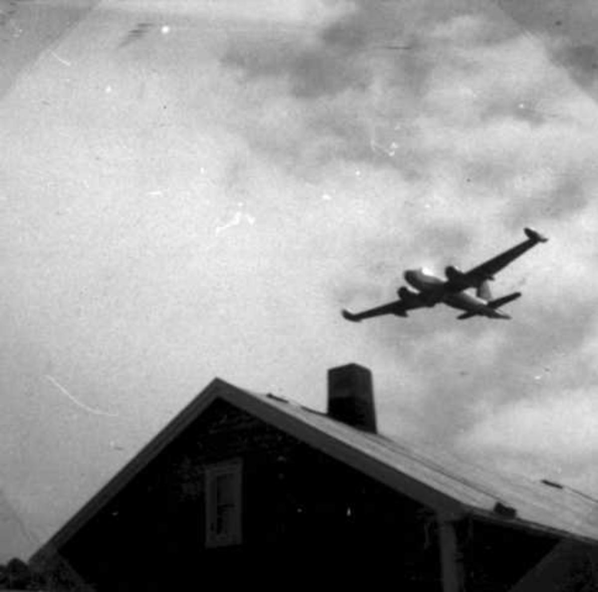 Ett fly i lufta, Lockheed P2V7 Neptune fra US NAVY, like over et hustak.