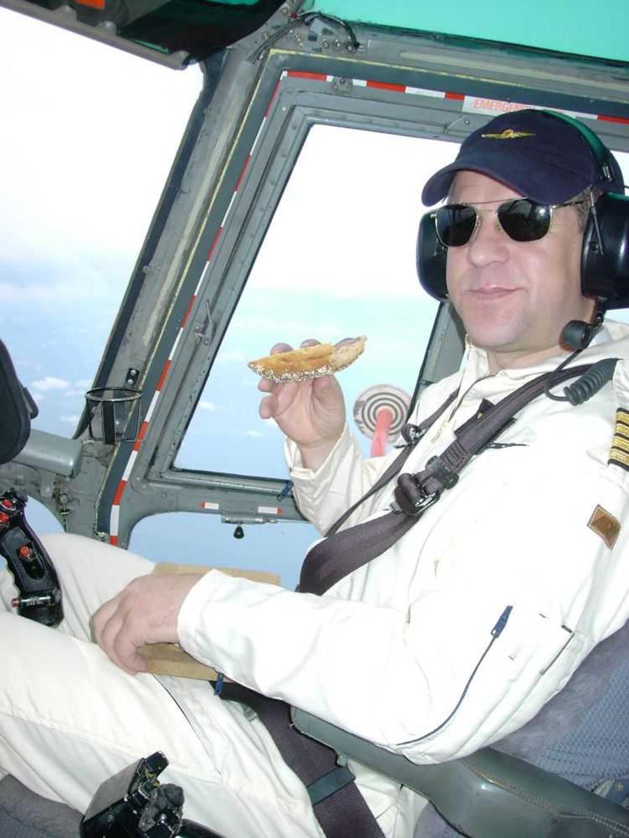 En person, flyger (pilott) sitter i cockpiten og spiser.