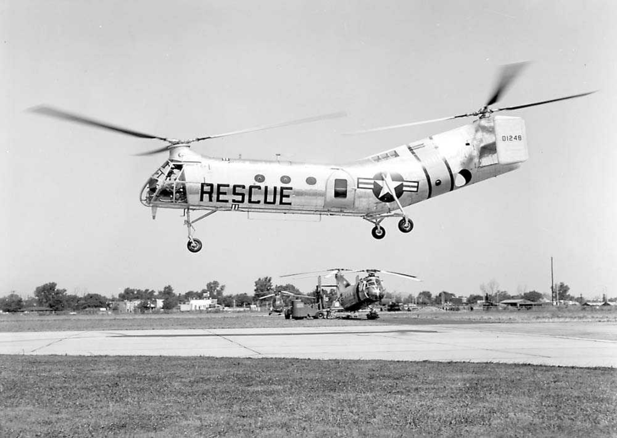 1 helikopter i luften. Piasecki H-21A. 2 helikoptere på bakken i bakgrunnen.