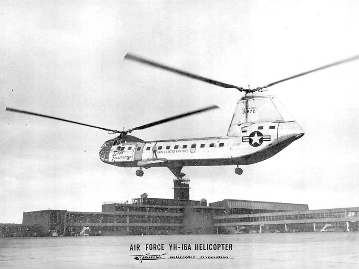1 helikopter i luften. Piasecki YH-16A. Flyplassterminal og flytårn i  bakgrunnen.