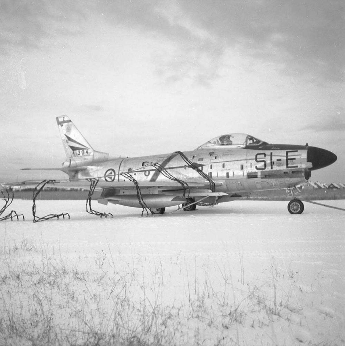 F-86-K, SI-E, tail nr. 54-1304, i nettet på Bodø flystasjon. Flyet tilhørte 339 skvadron, Bardufoss flystasjon. Se også NL.05060373.