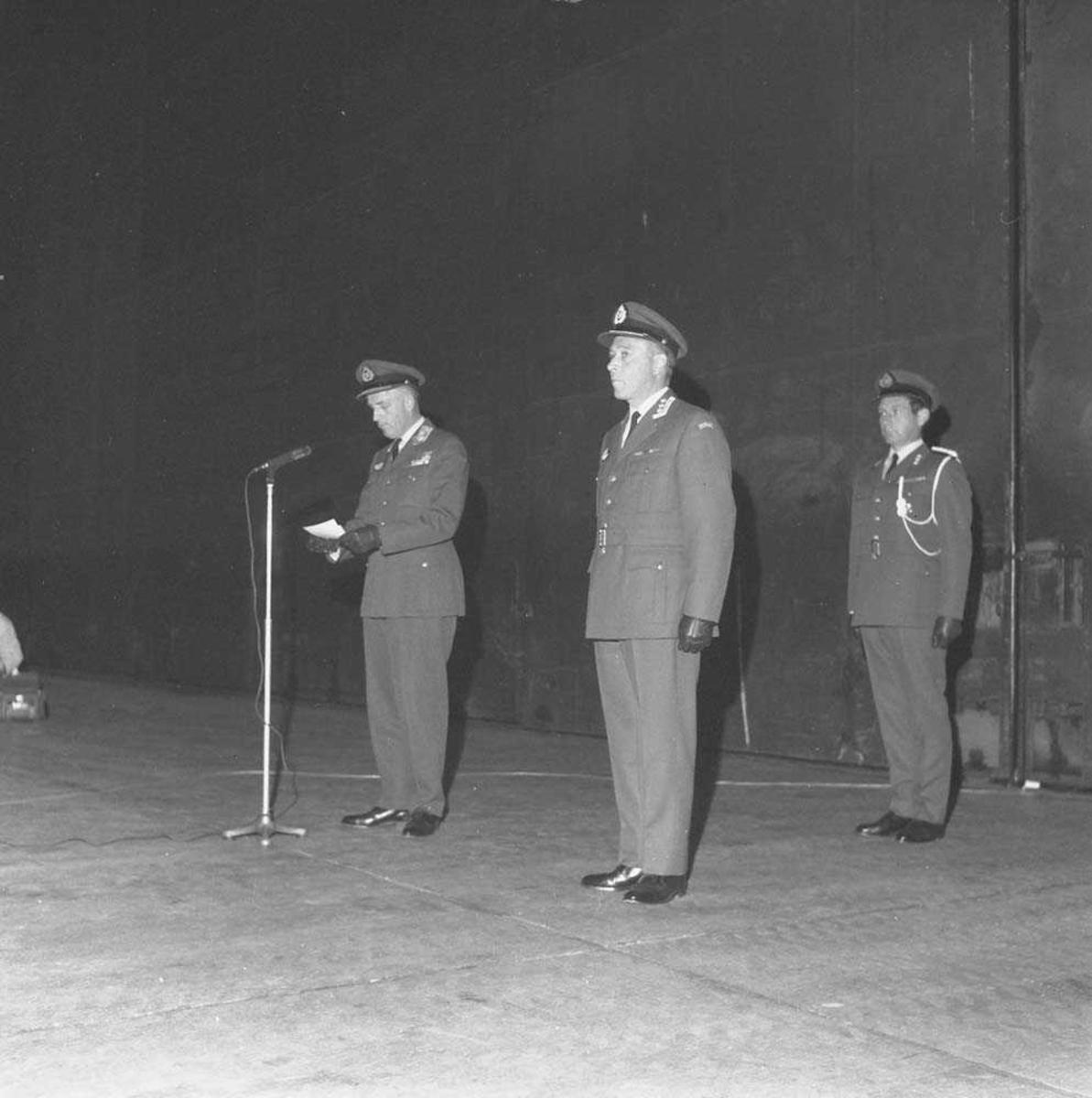Stasjonssjefskifte på Bodø flystasjon. Påtroppende sjef er Oberst K. Bjørge-Hansen, som står i midten av de 3 personene på bildet. Avtroppende sjef er Oberst E. Tjensvoll. Til venstre på bildet sees General W. Christie, som forestår sjefsskiftet.
