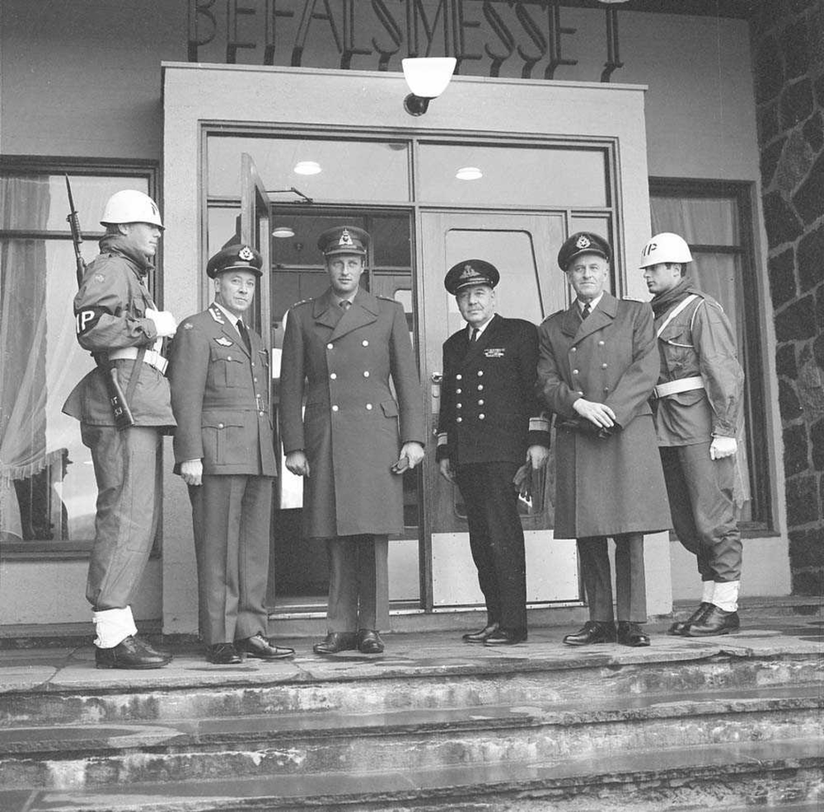 Hans Kongelige Høyhet Kronprins Harald besøker Bodø flystasjon. Fra venstre sees MP-vakt, Oberst K. Bjørge-Hansen, Kronprins Harald, Admiral R. Tamber (usikker), General W. Christie og MP-vakt.