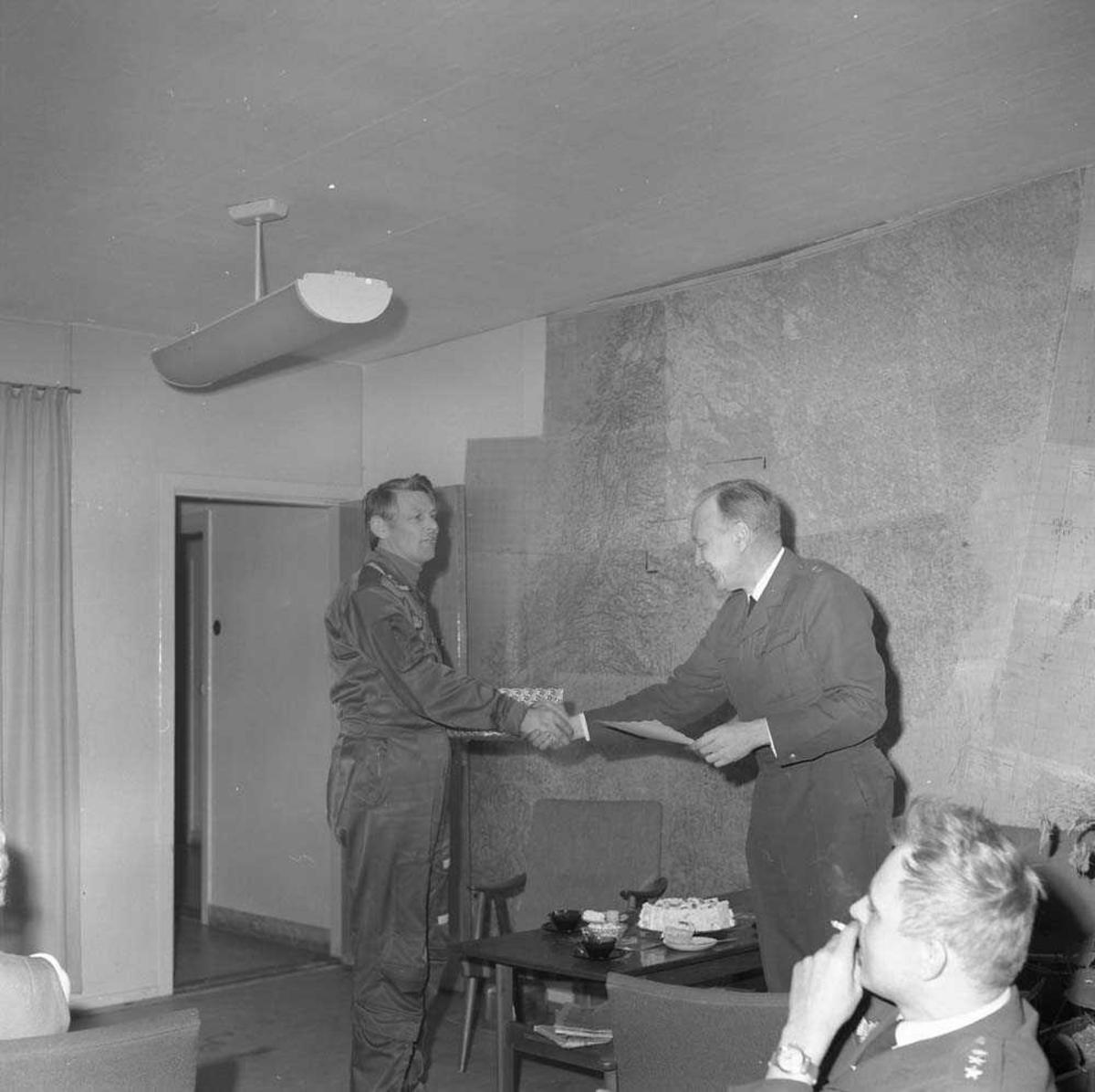 Løytnant Finn Bøe, Operasjonsgruppen, Bodø flystasjon, sees i midten og mottar gave av Oberstløytnant Alf Granviken. Sittende til høyre sees Kaptein Jan Erik Lie.