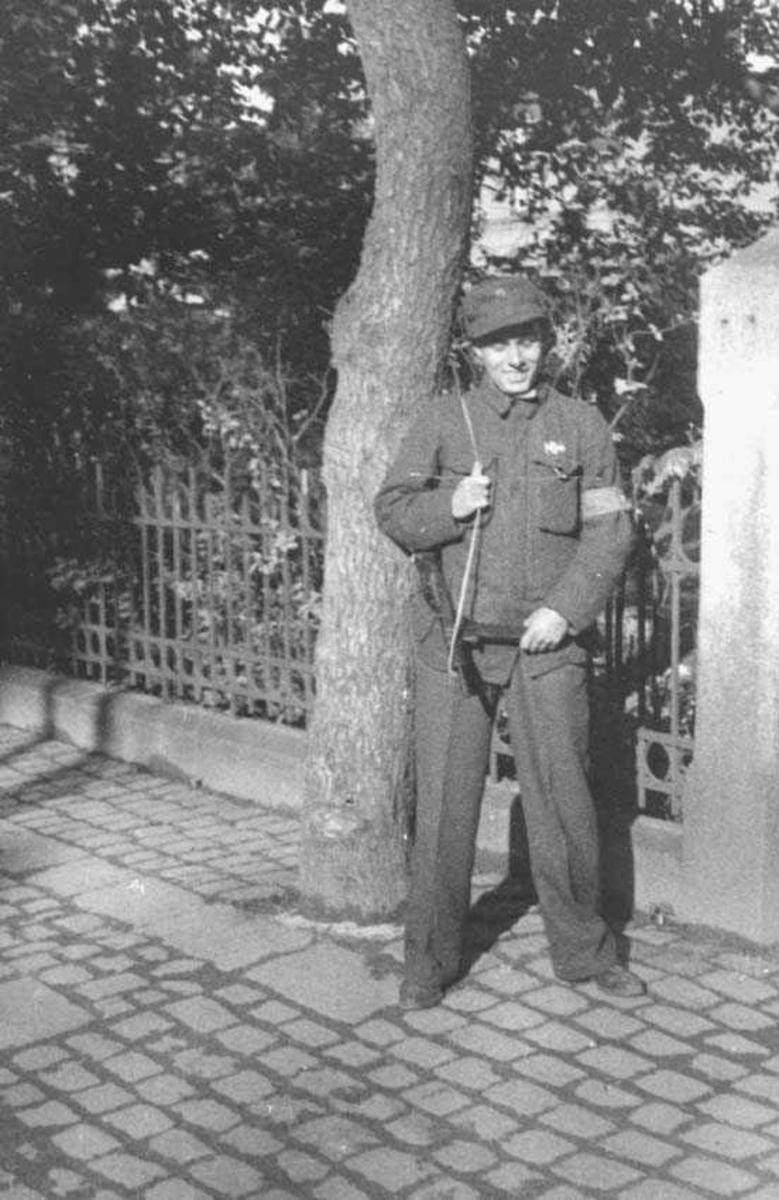 En person. Mann. Står vakt. Har på seg uniform og har et våpen hengene over ene skulderen.