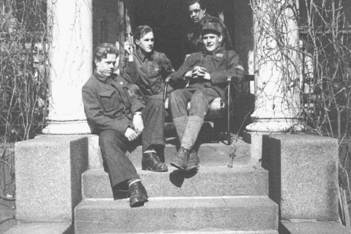 Fire personer. Menn. Sitter på et trapp. De har uniform på seg.
