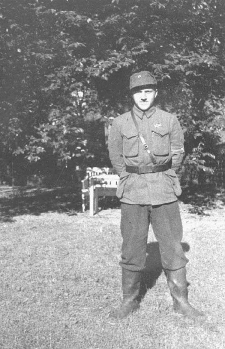 En person. Mann. Står ute i en hage. Har uniform på seg.