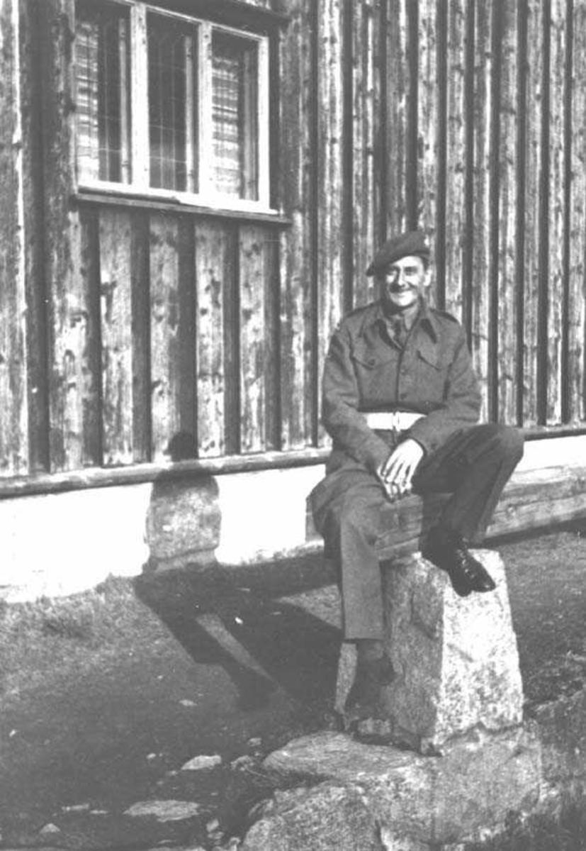 En person. Mann i militæruniform. Sitter på en stein foran en bygning.