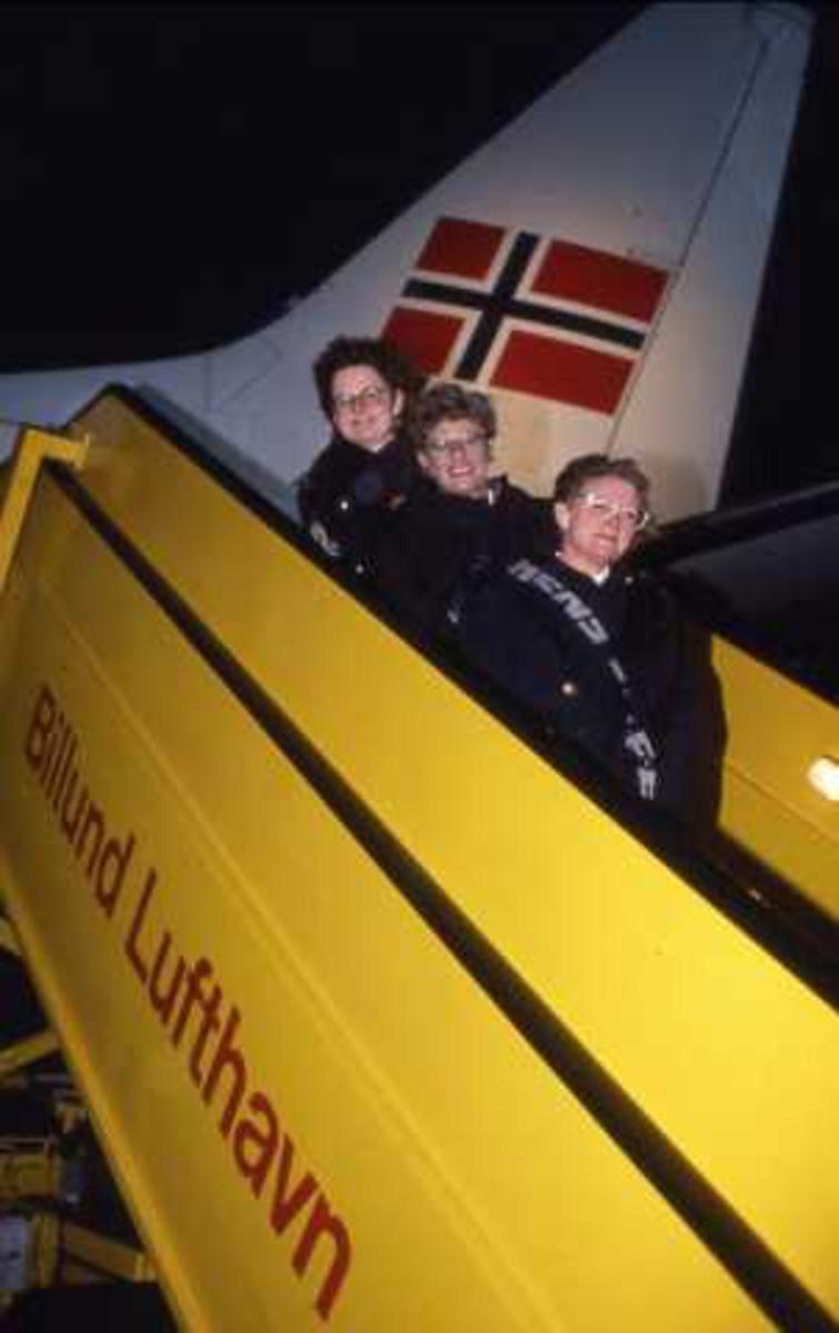 Ett fly på bakken. Tre personer ved flyet.