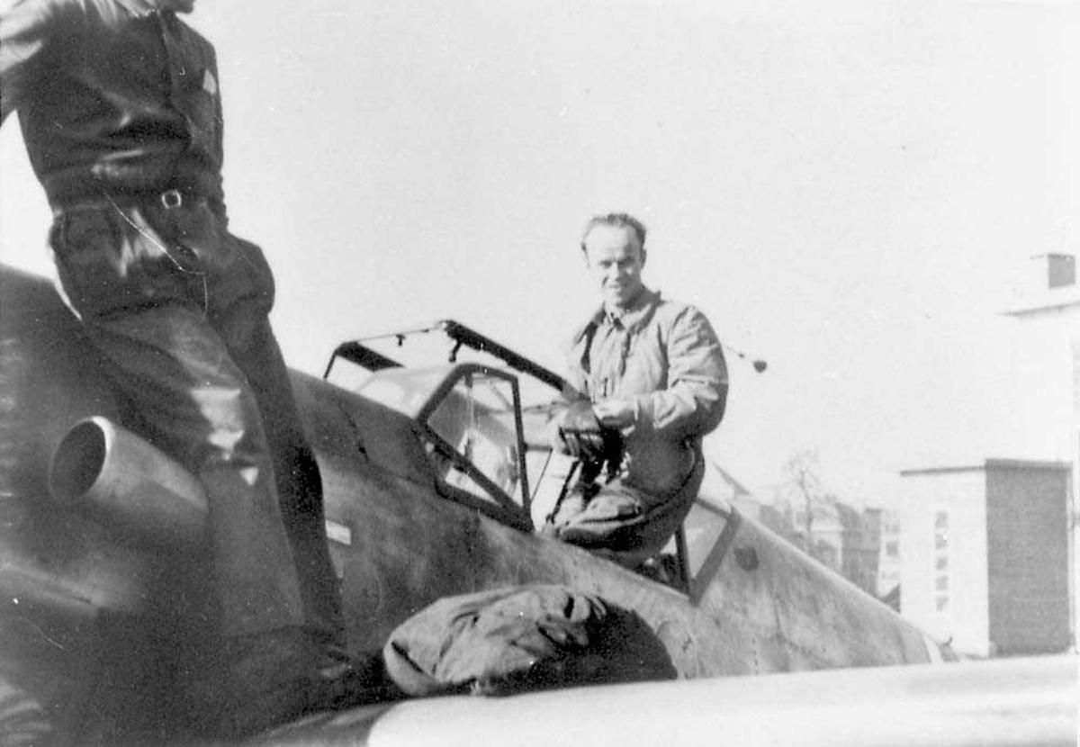 En person som sitter på kanten av cockpiten til et fly. Deler av en person som sitter foran cockpiten. Bygninger i bakgrunnen.