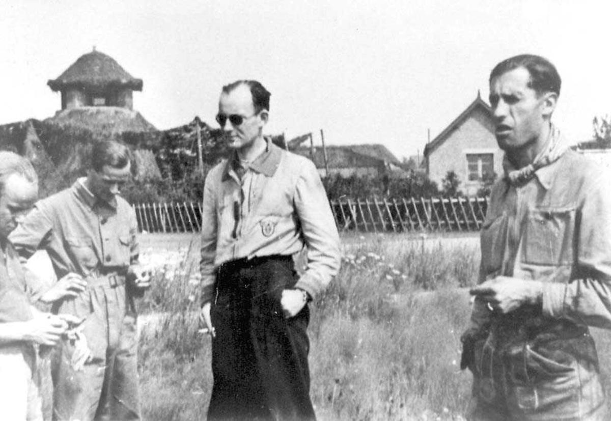Fire personer som står ute på en åpen plass. Bygninger i bakgrunnen.