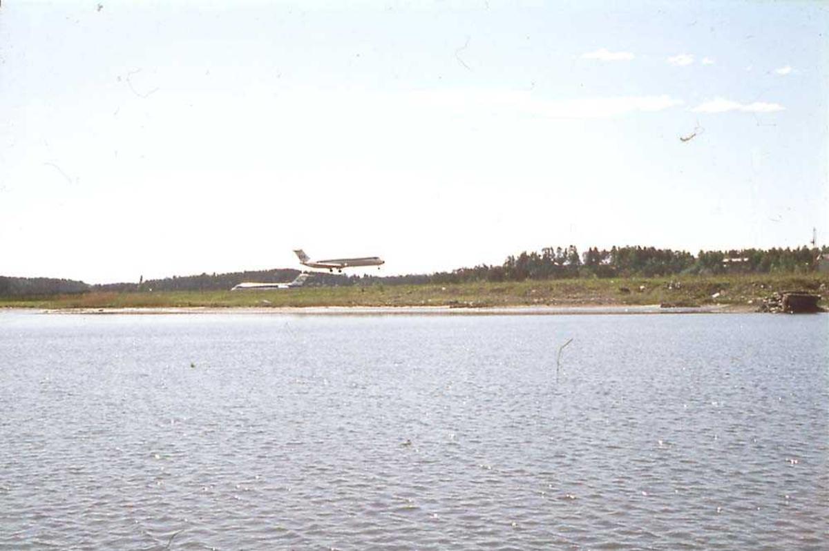 Luftfoto. Ett fly like før landing, McDonnell Douglas DC-9 -21/ -33/ -41 fra SAS. Ett annet på bakken i bakgrunnen.