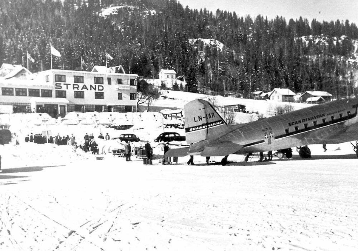 Ett fly på bakken, Douglas DC-3 / C-47 Dakota LN-IAR fra SAS. Flere personer ved flyet og i bakgrunnen. Bygninger og fjell i bakgrunnen. Snø på bakken.