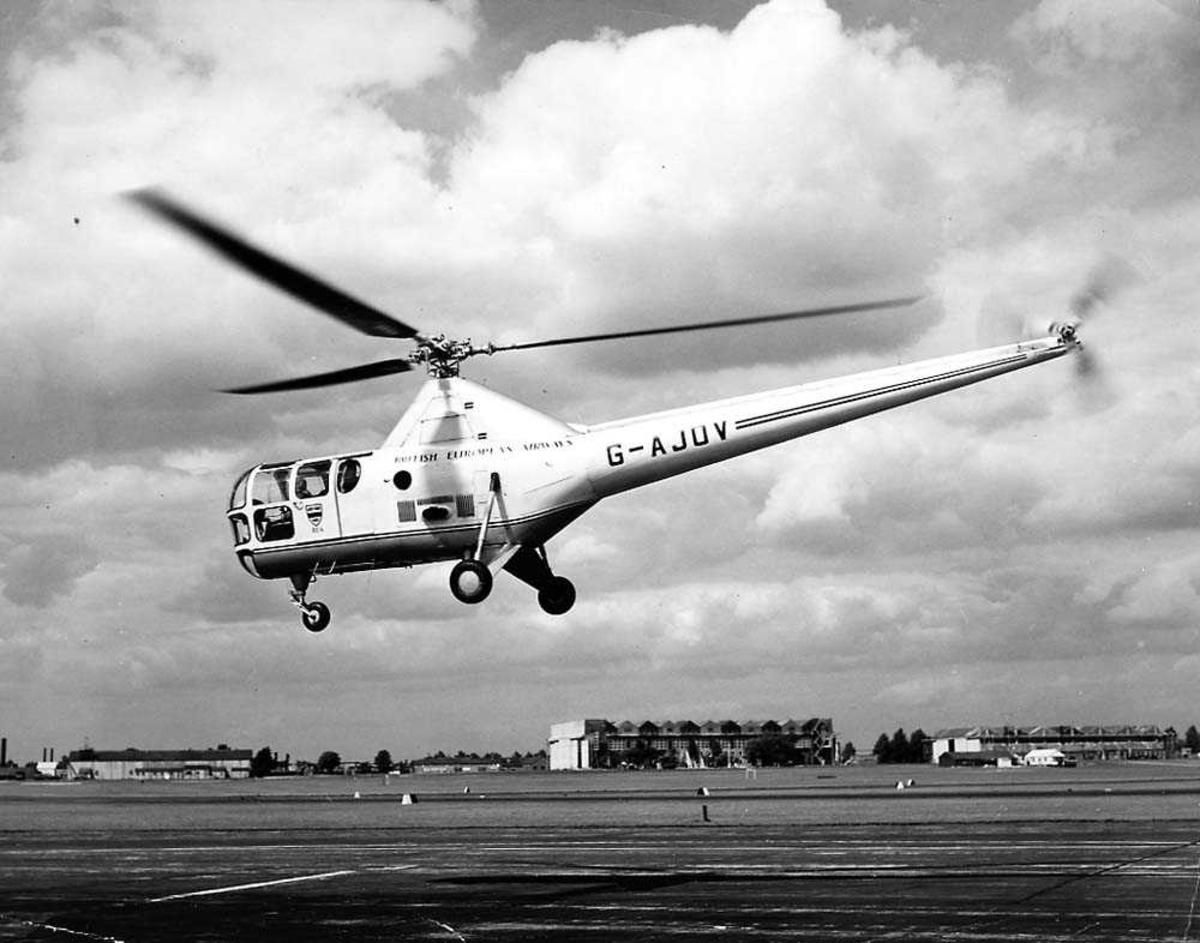Lufthavn. Ett helikopter i luften like over bakken, Sikorsky S-51 G-AJOV fra BEA. Bygninger i bakgrunnen.