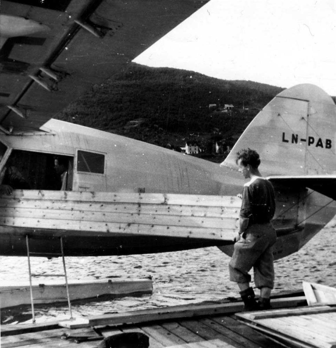 Ett fly som ligger på vannet ved en kai, Noorduyn Norseman VI-UC-64A-ND LN-PAB fra Polarfly. En person på kaien som laster noen treplanker inn/ut av flyet.