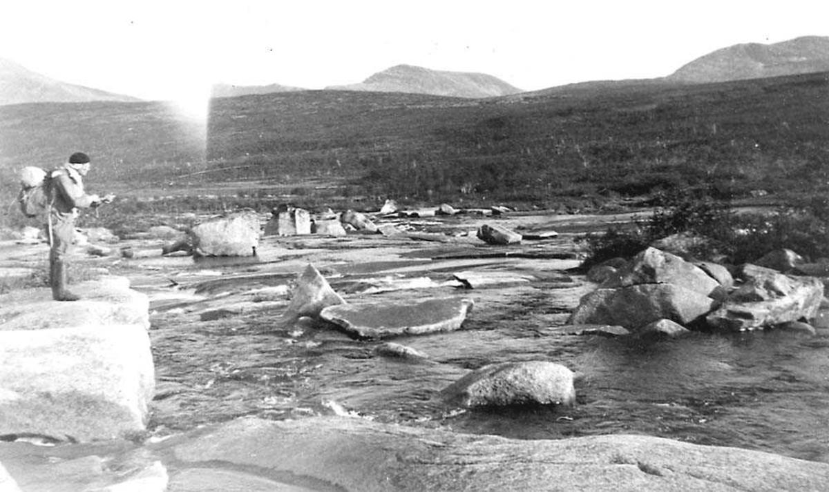 En person som står på en stein i ei elv og fisker. Fjell i bakgrunnen.