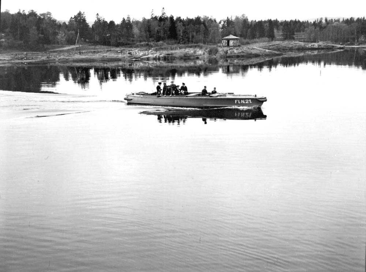 Flere personer i militæruniform ombord i en båt ute på vannet.