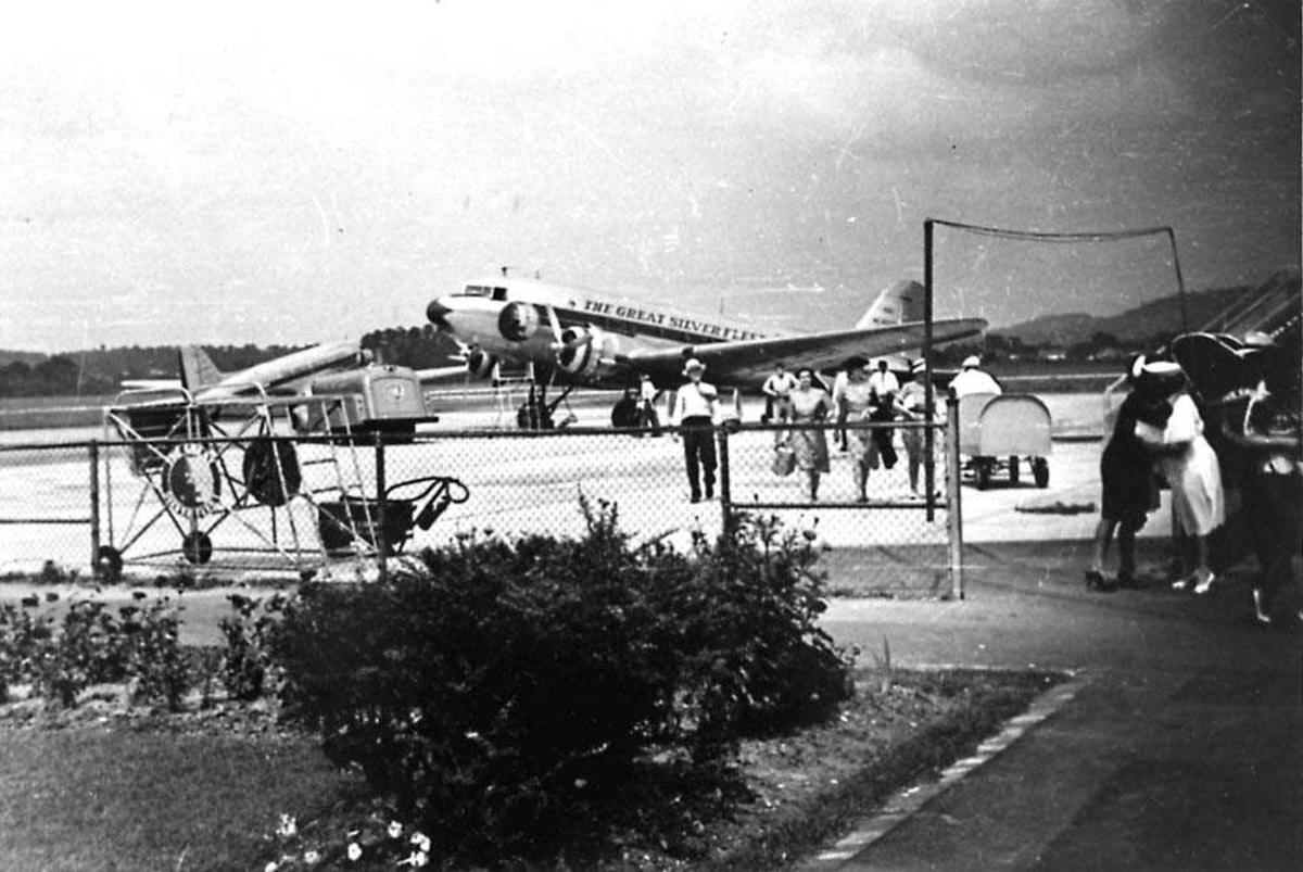 Lufthavn. To fly på bakken. Flere passasjerer på vei fra det ene flyet.