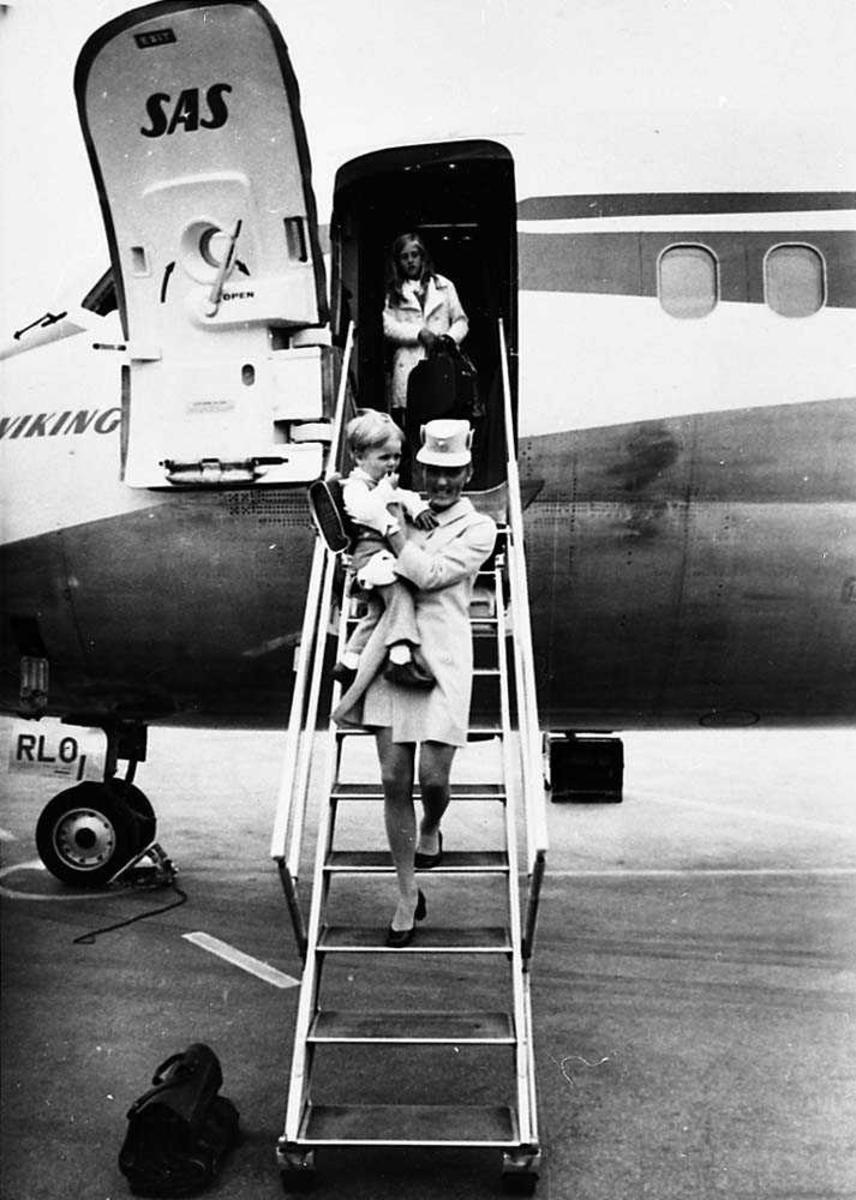 """Lufthavn. En flyvertinne på vei nedover en flytrapp med et barn i armene. Et person i døråpningen til flyet, McDonnell Douglas DC-9-21 LN-RLO """"Gunder Viking"""" fra SAS."""
