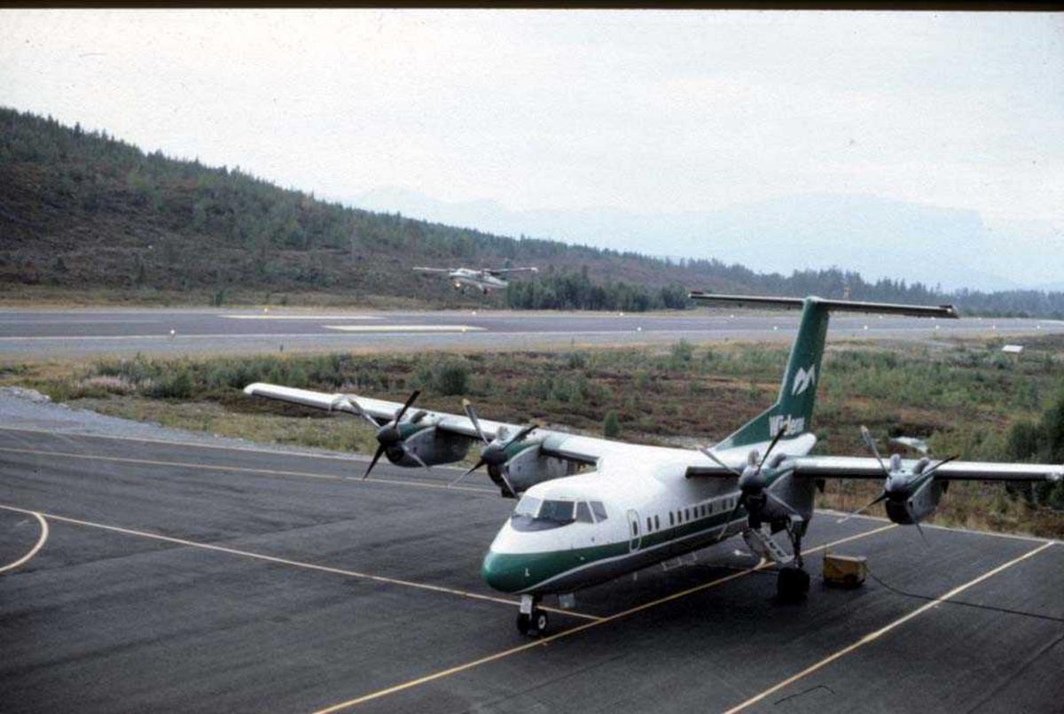Lufthavn/flyplass. Sandane. Ett fly, LN-WFL, De Havilland Canada DHC-7-102 Dash7 fra Widerøe, parkert. Ett fly, DHC-6-300 Twin Otter fra Widerøe, take off.