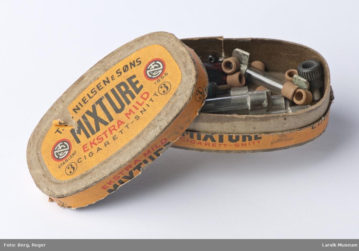 Eske inneholder diverse skruer sikringer og segllakk til senderen.