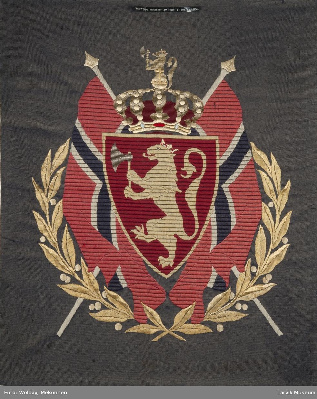 Våpenet omgitt av norske flagg og to laurbærgrener i en krans