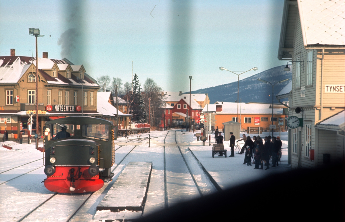 Tynset jernbanestasjon sett fra lokomotivet i Ht 301 (Dagtoget). Skiftetraktor type 214 i spor 2. Reisende venter på plattformen, og utvendig stasjonspersonale står klar med reisegods.