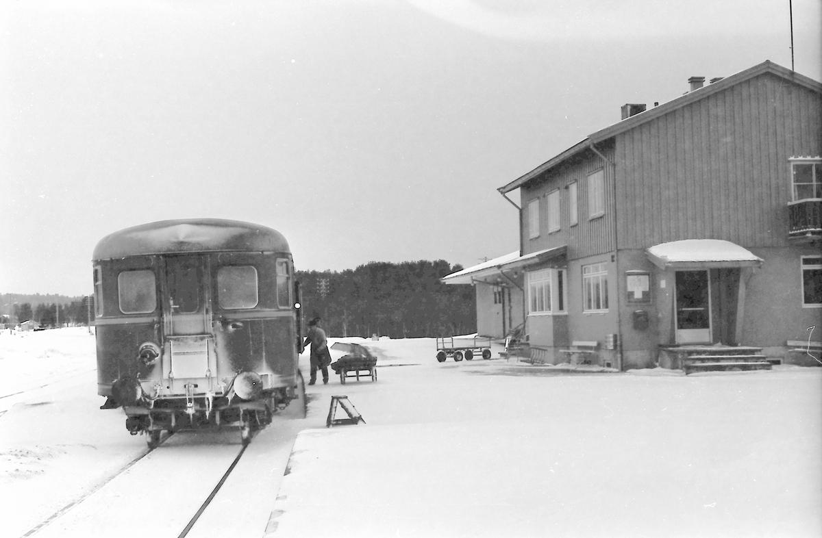 Tog 371 (Hamar - Røros) på Os stasjon. Posten lempes ut av betjent postvogn. Styrevogn BDFS 91 71 eller 91 73. Os i Østerdalen.