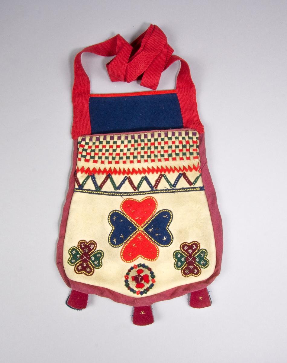 Kjolsäck troligen inspirerad av kjolsäckar från Dalarna, svårbedömt ursprung. Modell med avskuret framstycke. Tillverkad av ljust sämskskinn med applikationer av ylletyg, kläde, i rött, mörkblått, mörkrött och grönt, fastsydda med läggsöm i gult. Centralt placerad hjärtblomma med mindre hjärtblommor i hörnen samt en rundel mellan dem, spår av två rundlar till. Ovanför applikationen en längsgående sicksackrand och ovan den ett flätat parti, gjort av smala remsor sämskskinn och rött, grönt och blårött kläde; nedtill med tandad kant och underlägg av tandad remsa rött kläde. Broderi utfört med bomullsgarn i vitt: sticksöm. Inlägg i sido- och bottensöm med remsa av blårött bomullstyg, kypert. I bottensömmen tre tofsar av blårött, grått och mörkblått kläde. Bakstycke och foder av mörkblått kläde. Axelband av rött diagonalvävt ylleband.