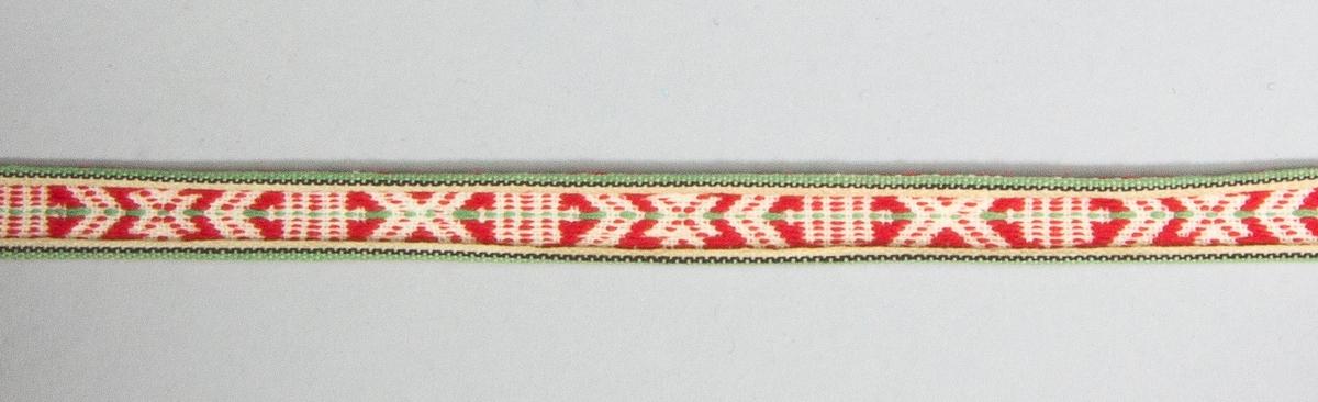 Kjolsäck till dräkt för kvinna från Leksands socken, Dalarna. Modell med u-formad öppning. Tillverkad av svart ylletyg, kläde, med applikation av kläde i rött, gult och grönt, fastsydd med läggsöm. Centralt placerad hjärtblomma med slingor och trekanter på sidorna. Broderi utfört med bomullsgarn i flera färger: flätsöm och sticksöm. Framstycket fodrat med grått bomullstyg, tuskaft. Kantat runtom med rött diagonalvävt ylleband. Bakstycke av svart kläde. Midjeband fabriksvävt, med rött mönster på vit botten, hake och hyska.