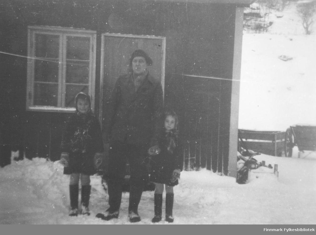 Evald Valen og hans to døtre?, står foran butikkbrakka i Lillefjord. Det er vinter og snøen ligger på bakken. De er godt kledt. Til høyre for brakka, står en kjerre