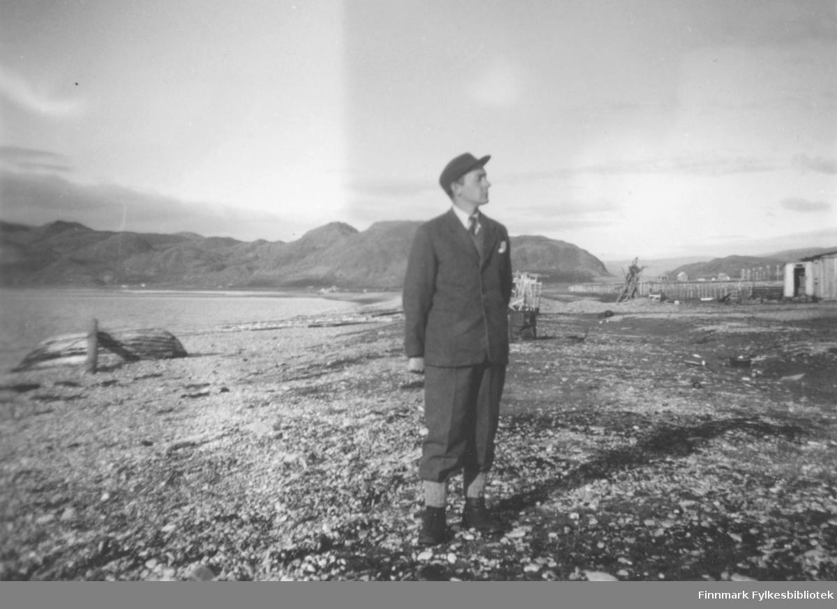 Anders Ydstie som poserer ovenfor fjæra i Kokelv. Han var lærer i Kokelv i mange år. Det ligger en hvelvet båt til venstre for han. Til høyre ses en bygning. Det er fjell i bakgrunnen