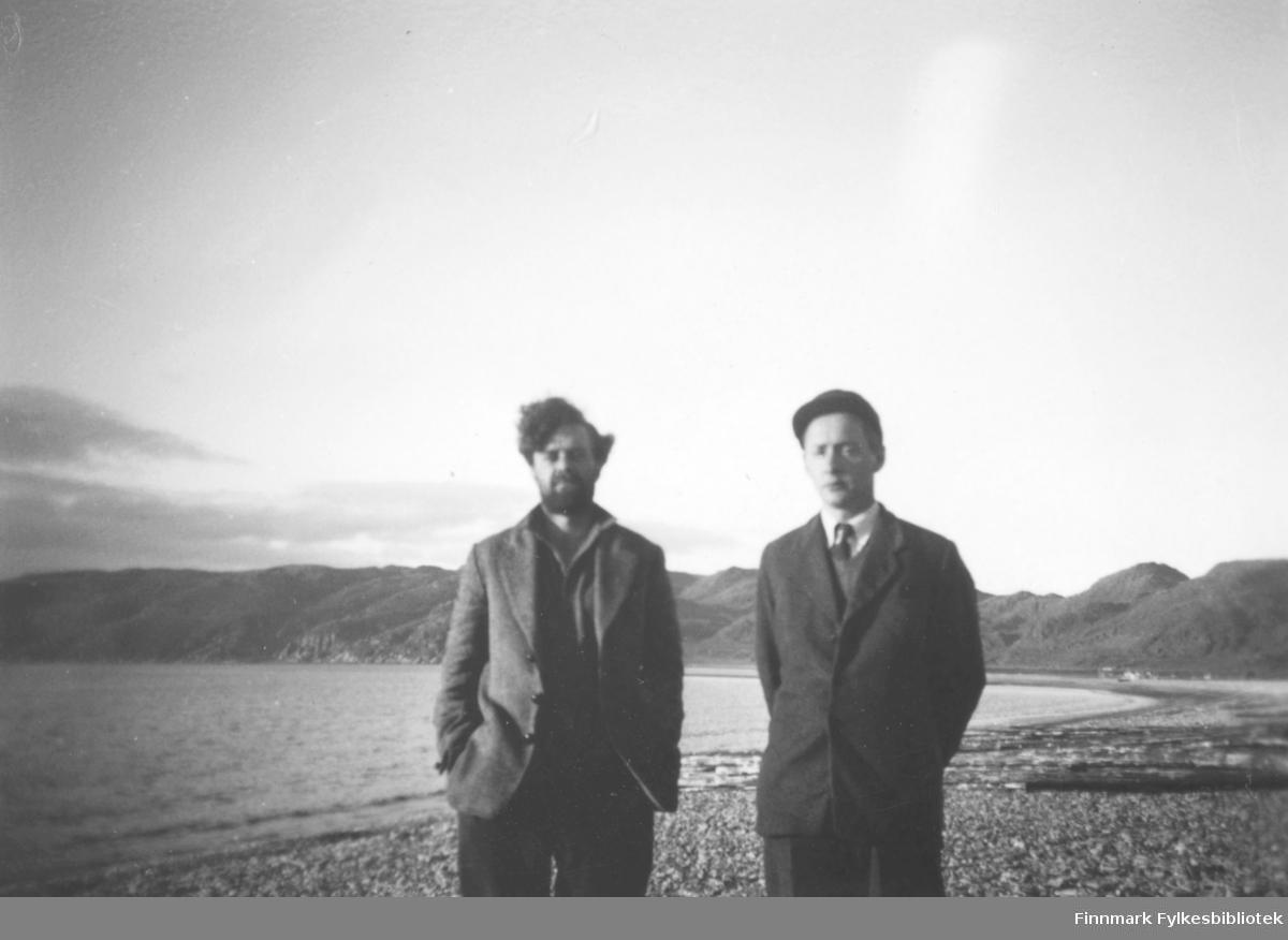 Den engelske antropologen Robert Paine til venstre, og lærer Anders Ydstie poserer i fjæra. Fjellene ses i bakgrunnen