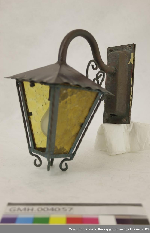 Lampen er en vegglampe for utebruk. Den monteres ved å skru en holdeplate fast i veggen som strømledningen føres gjennom. Holdeplaten har en gjengestav i hvert hjørne. Lampen festes til platen ved å føre gjengene gjennom hullene og feste med muttere. Disse har avrundede hoder. Strømledningen går gjennom lampearmen som er bøyd og pyntet med to spiralformede staver i S- og C-form. Grunnformen til lampeskjermen er rektangulær med med bøyde kanter. Lampekroppen blir smalere i underkant ogmetallrammen huser gule, mønstrede ruter i hamret glass med omvendt trapesform. På innsiden av lampeskjermen befinner det seg innfatning til en lyspære med størrelse E27. For å skifte lyspæren, kan lamperammen skrus løs fra skjermen på framsiden. På baksiden er delene hengslet sammen.