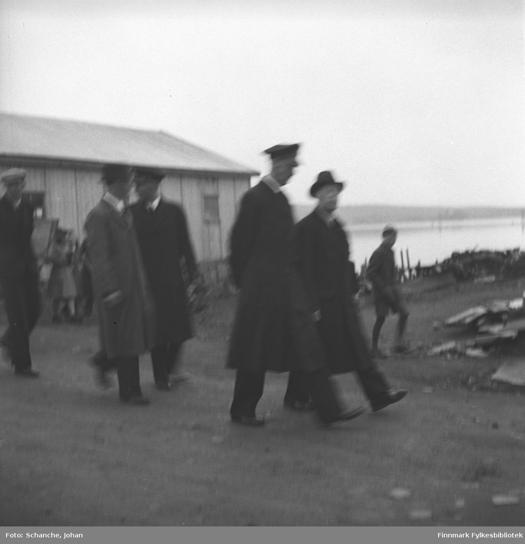 Kongebesøk: Kong Haakon VII og fylkesmann Hans Gabrielsen går på gata i Vadsø.  Folkemengde har samlet seg langs veikanten, flagger. Byens sentrum ligger ennå i ruiner.