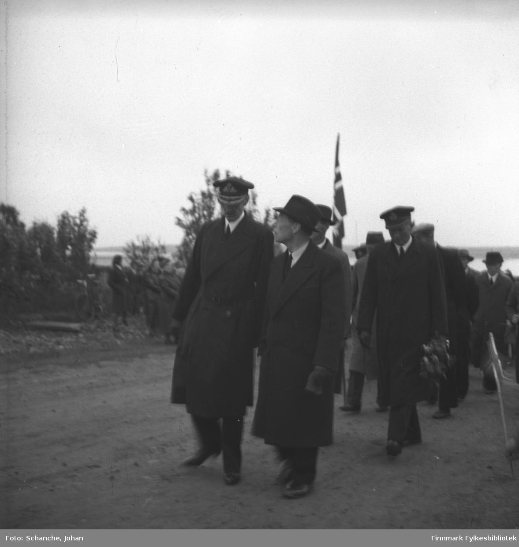 Kong Haakons besøk i Vadsø i 1946. Kong Haakon VII, fylkesmann Hans Gabrielsen og adjutant kommandørkaptein Bruusgaard  (med blomsterbukett i hand) går langs gata i Vadsø. Folkemengde på vegkanten.