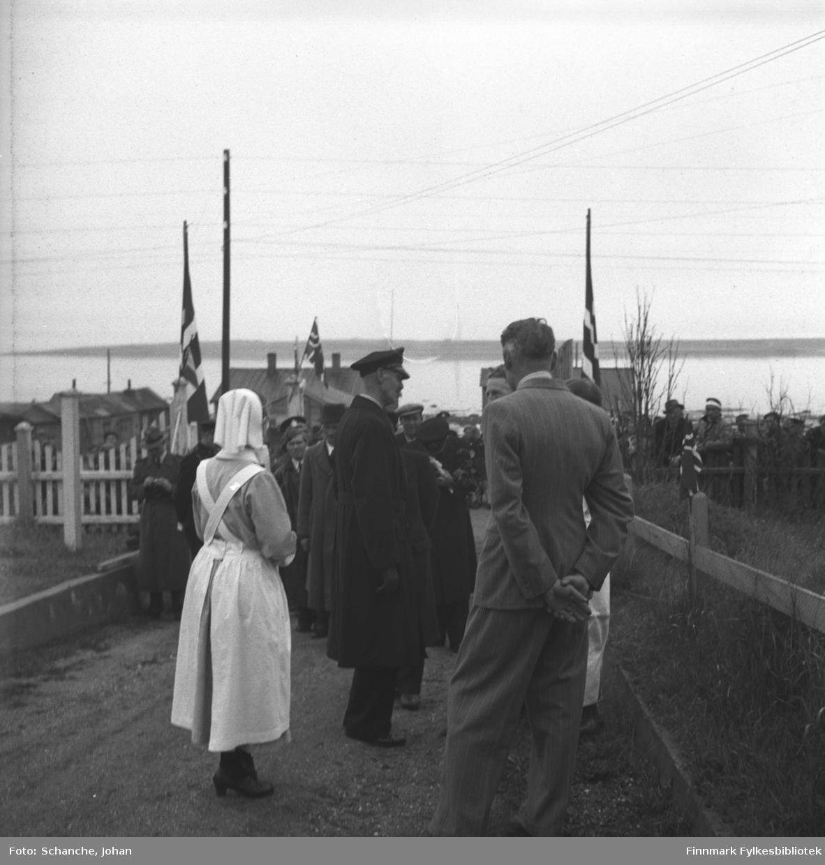 Kongebesøk:  Kong Haakon VII besøker sykehuset i Vadsø. Kongen står med noen menn og oversøster Anna Aase ved porten til sykehuset. Bak dem står Kongens følge og lengre bort på gata folk fra Vadsø. På bakgrunn en del av byen og lengst bort skimtes Varangerfjorden.
