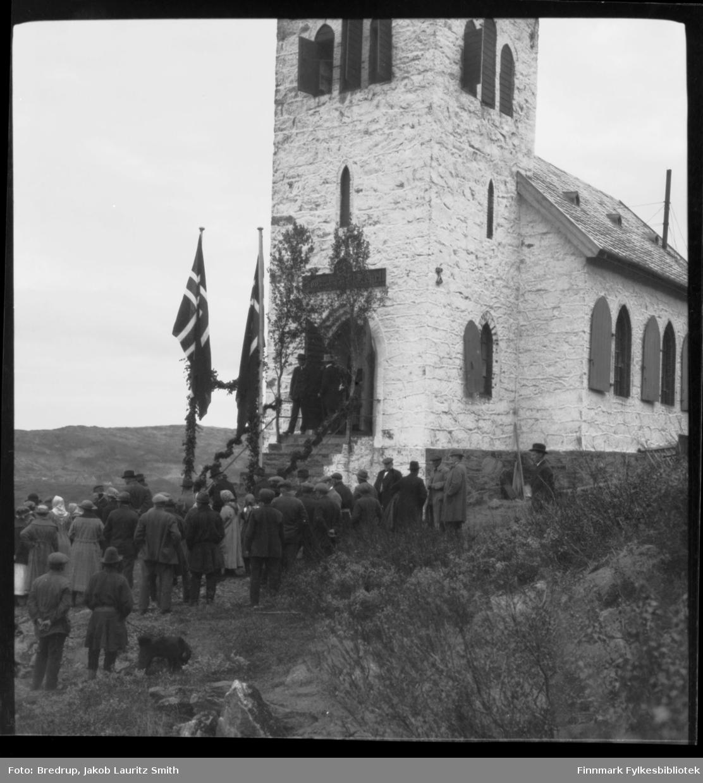 En gruppe samlet foran Oscar II kapell i Grense Jakobselv.  De fleste står med ryggen mot fotografen, to menn står på trappa.  Noen har samekofter på seg.  De fleste ser ned mot elva.  Kapellet er pyntet med bjørkeløv og flagg.