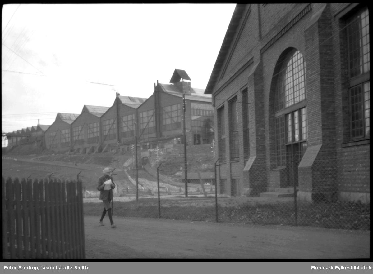 Bildet er tatt med Dampsentralen i forgrunnen opp mot Separasjonsverket til A/S Sydvaranger.  En ung mann i nikkers og poselue går travel med papirer i hendene i retning Dampsentralen.