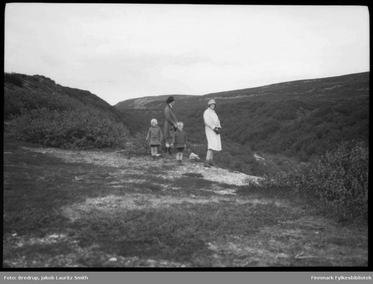 To kvinner og to barn på tur.  På bildet står de på en høyde og ser ned på en liten elv som renner i dalbunnen.  Vi vet ikke hvor bildet er tatt, eller hvem personene er.  Men terrenget minner om Tomaselvdalen.