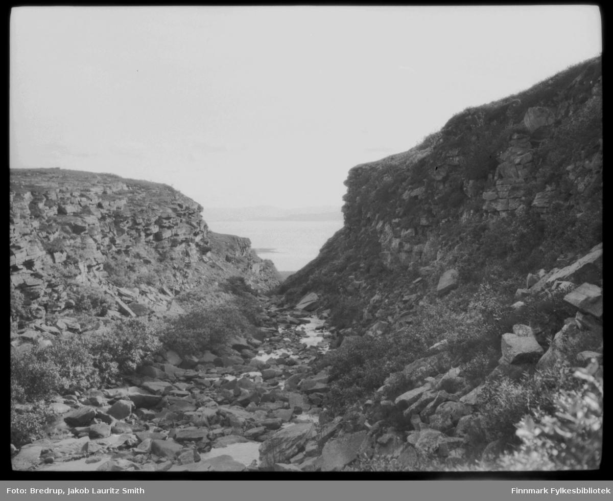 Fotografen har stått i et lite fjellskar og fotografert ned mot en fjord.  Vi vet ikke hvor bildet er tatt, men landskapet og vegetasjon ligner veldig på Varanger.