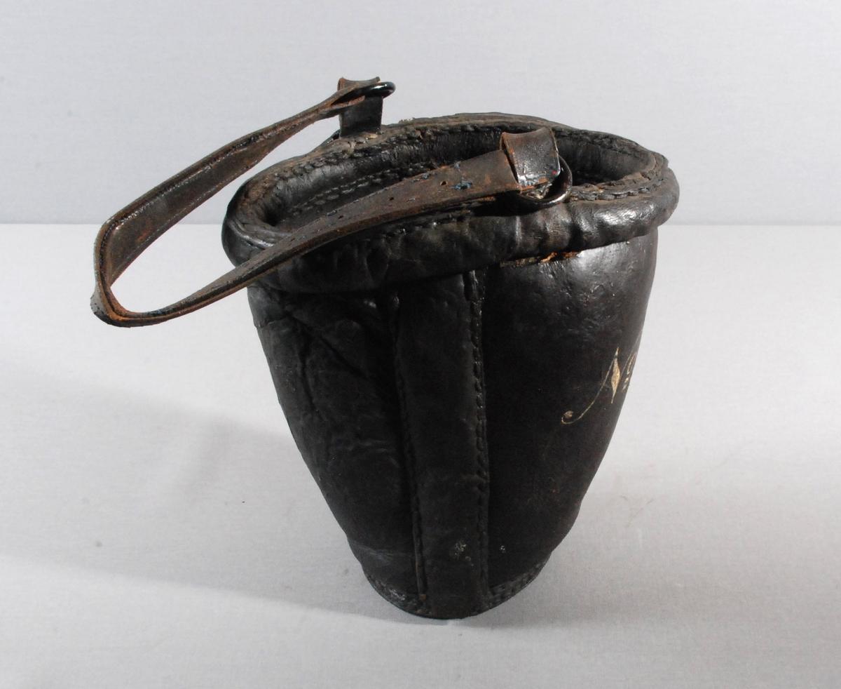 Brannbøtte i lær med lærhank. Hanken har metallringer i begge ender, som er tredd inn i lærhemper som er sydd fast i overkant av bøtten.