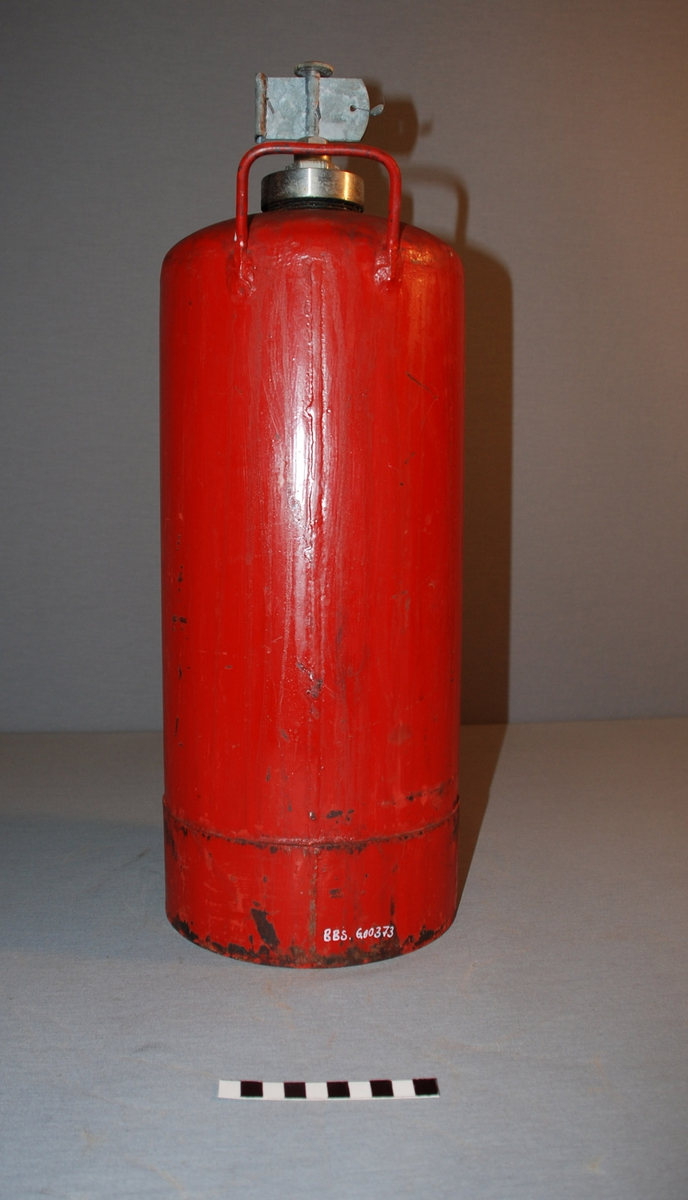 Vannapparat. Sylindrisk beholder avrundet mot toppen, der det er en ventil . Øverst på siden av beholderen en metall styss for slange. Håndtak øverst på siden av beholderen.