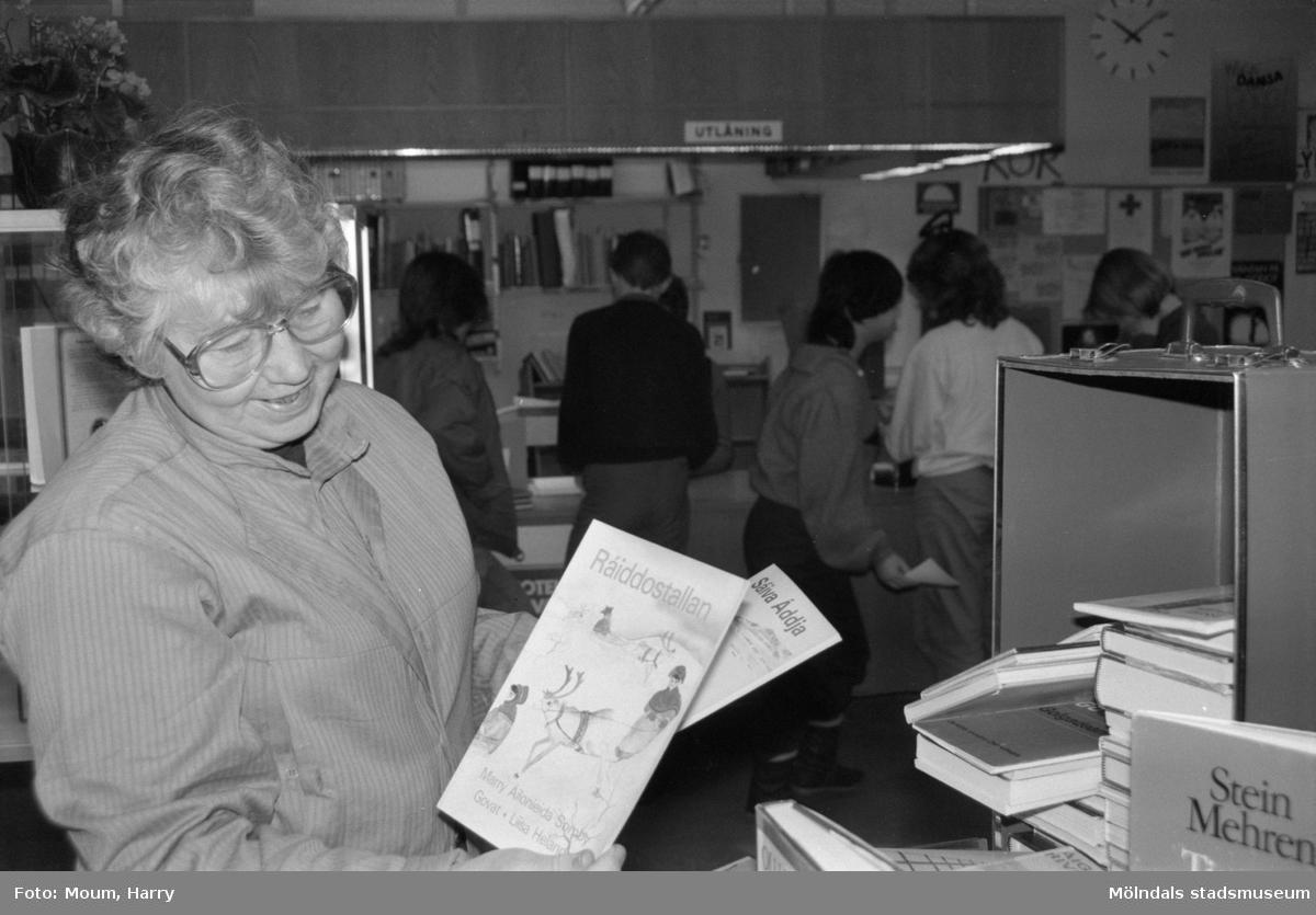 """Utställning med nordiska böcker på Lindome bibliotek, år 1985. """"(?) Heimann vid Lindome bibliotek plockar fram utställningsmaterial till """"Nordiska böcker"""".""""  För mer information om bilden se under tilläggsinformation."""