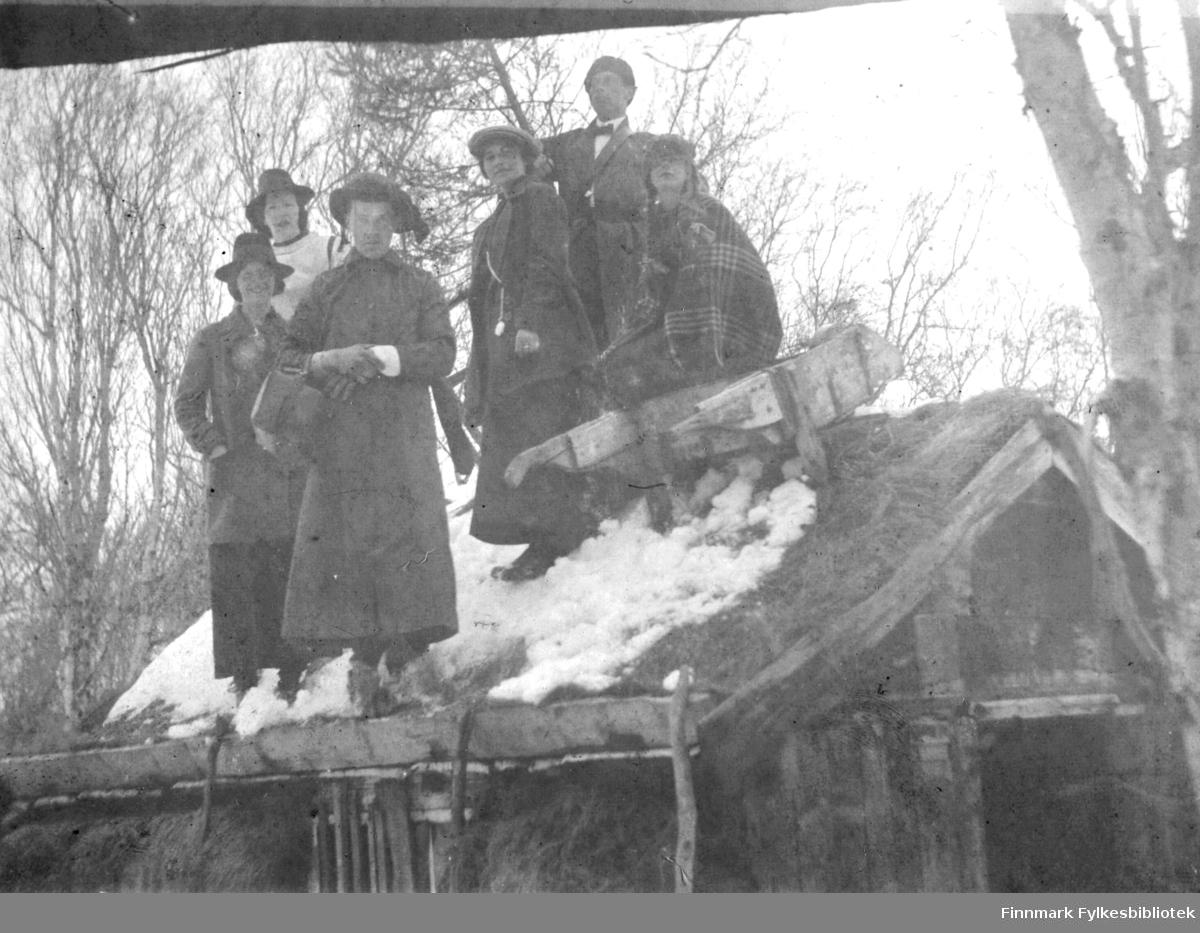 Gruppebilde fotografert på et tak, antakelig i Tana. I forgrunnen en mann utkledd som kvinne, i bakgrunnen ei jente som også ser ut til å ha kledd seg ut