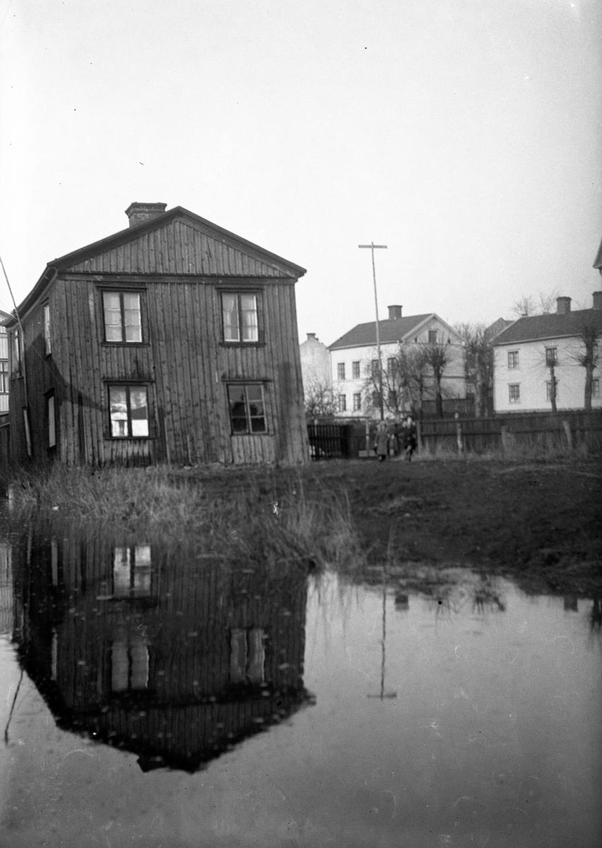 Bostadshus med en stor vattensamling i förgrunden.